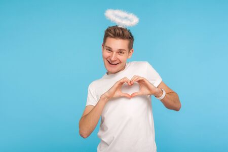 Portrait of happy angelic man with halo above head making heart shape with hands and smiling to camera, sharing romantic amorous feelings, declaration of love. studio shot isolated on blue background