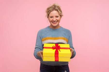 Portrait of happy excited woman with short curly hair in warm sweater holding wrapped present box and smiling at camera, showing winter holiday gift. indoor studio shot isolated on pink background