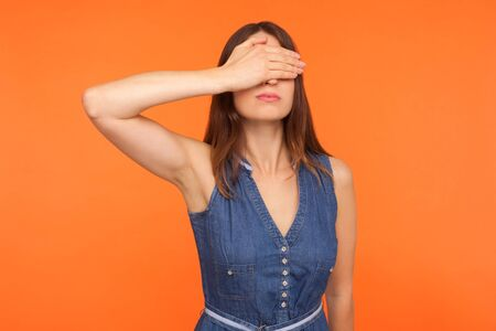 Dont want to look. Young brunette woman in denim dress covering eyes with hand, rejecting to watch forbidden inappropriate content, ignoring problems. indoor studio shot isolated on orange background