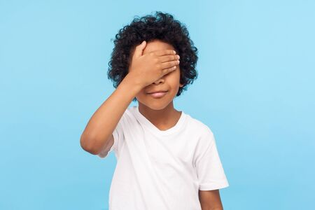 I'm not watching. Portrait of cute little boy with curls covering eyes with hand not to look at something forbidden, hiding eyes playing peek a boo. indoor studio shot isolated on blue background