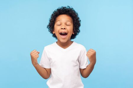 Child winning, success. Portrait of excited little boy in T-shirt raising hands and screaming delighted with victory and luck, expressing extreme joy. indoor studio shot isolated on blue background