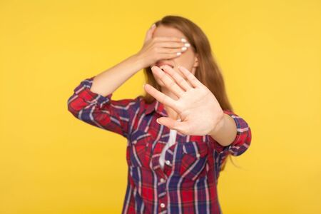 No, I don't want to look. Portrait of girl in shirt covering eyes with hand and showing stop, ban block gesture, being surprised and scared avoiding to watch. studio shot isolated on yellow background