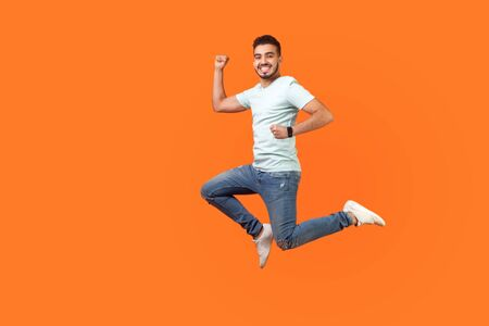 Full length portrait of positive inspired brunette man with beard in sneakers, denim outfit jumping in air or running quickly fast. indoor studio shot isolated on orange background, empty copy space Banco de Imagens