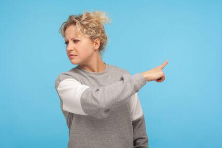 ¡Déjame! Mujer resentida con el pelo rizado en sudadera apuntando hacia los lados, mostrando gesto de salir, ordenando irse, sintiéndose molesta y disgustada. Foto de estudio de interior aislado sobre fondo azul.