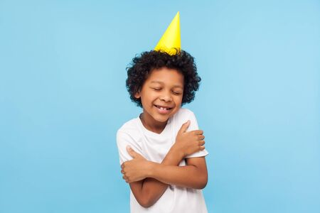 I love and congratulate myself. Portrait of amazing lovely kid with funny party cone embracing himself and smiling from pleasure, happy to celebrate birthday alone. indoor studio shot blue background