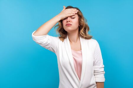 Facepalm. Portrait of forgetful woman with wavy hair in white jacket slapping hand on forehead, feeling sorrow regret about forgotten event, bad memory. indoor studio shot isolated on blue background
