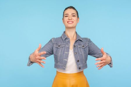 Portrait of friendly cheerful fashionably dressed woman with hair bun stretching hands to camera, going to embrace, giving warm welcome. studio shot isolated on blue background