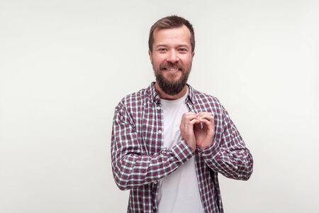 Portrait of heartful kind bearded man in casual plaid shirt smiling and making heart gesture with hands, expressing feeling of love affection friendship. indoor studio shot isolated, white background