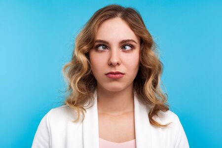 Closeup portrait of adorable funny woman with wavy hair in white jacket looking cross-eyed with awkward silly dumb face expression, squinting eyes. indoor studio shot isolated on blue background