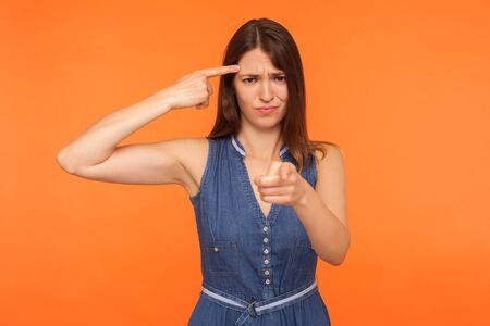 Positive brunette woman in denim dress holding finger near head temple and showing stupid gesture, pointing to camera with mocking expression. studio shot isolated on orange background Banco de Imagens