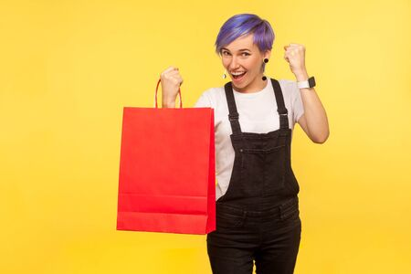 Portrait of joyful buyer, nice girl with violet short hair in denim overalls holding packages and raising fist saying yes i did it, enjoying shopping with discounts sale. yellow background studio shot Stok Fotoğraf