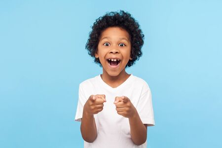 Portrait of happy little boy with curly hair pointing finger to camera and laughing loudly with surprised face, teasing making fun of you. indoor studio shot isolated on blue background Reklamní fotografie