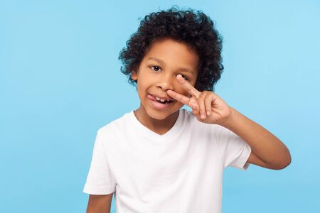Portrait of cheerful carefree little boy with curly hair in T-shirt picking nose and sticking out tongue with happy face, having fun, bad manners concept. studio shot isolated on blue background Foto de archivo