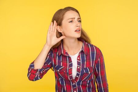 Portrait of attentive ginger girl in checkered shirt holding hand near ear trying to listen quiet conversation, overhearing gossip. indoor studio shot isolated on yellow background 版權商用圖片