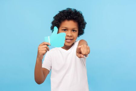 Portrait of wonderful happy preschool boy holding blue Like icon in his arm and pointing to camera, gesturing hey you comment and appreciate blog, trendy children content. studio shot blue background