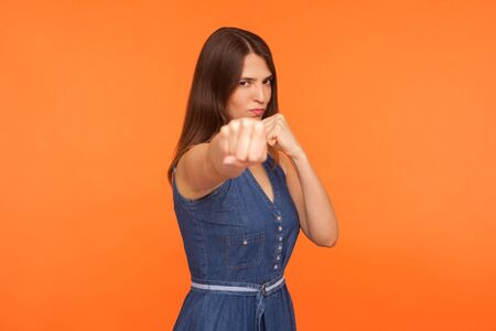 Determined brunette girl with fighting spirit in casual dress punching with fists, boxing, looking confidently at camera, strong woman defending herself. studio shot isolated on orange background Фото со стока