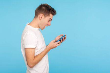 Side view of amazed astonished man in t-shirt using cellphone with surprised expression, shocked by message in social network, mobile communication. indoor studio shot isolated on blue background