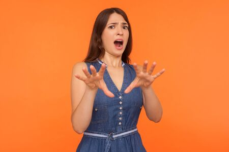 Frightened brunette woman in denim dress standing with raised hands, shouting in fear and looking startled at camera, shocked scared by danger. studio shot isolated on orange background