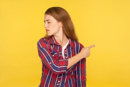 Conflict and breakup. Portrait of irritated ginger girl in checkered shirt turning away and showing gesture get out, asking to leave, feeling betrayed. indoor studio shot isolated on yellow background
