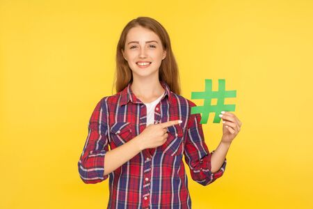 Social media trend, blogging. Portrait of ginger girl in checkered shirt pointing at green paper hashtag, showing hash sign and smiling at camera. indoor studio shot isolated on yellow background