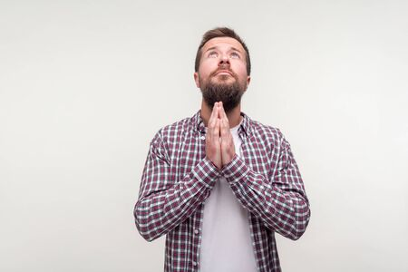 Portrait of upset bearded man in plaid shirt looking up and making prayer gesture with hands, apologizing saying please, desperate upset expression. indoor studio shot isolated on white background Фото со стока
