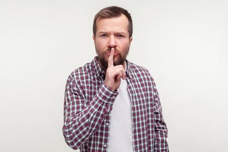 Be quiet! Portrait of strict serious bearded man in plaid shirt making hush silence gesture with finger on lips, frowning looking dissatisfied irritated. indoor studio shot isolated, white background