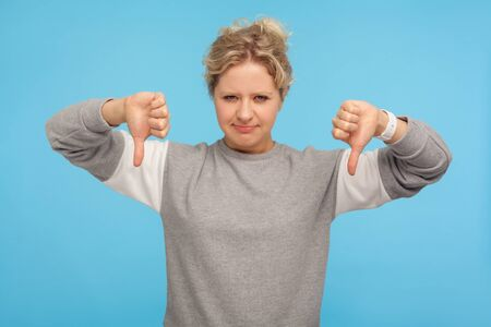 I don't like this! Naughty displeased woman with short curly hair in sweatshirt showing thumbs down, disapproval sign, dissatisfied with bad result. indoor studio shot isolated on blue background Banco de Imagens