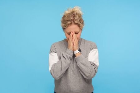 Depressed woman with short curly hair in casual sweatshirt hiding face down in hands and crying, hard going through loss or defeat, feeling sorrow. indoor studio shot isolated on blue background 版權商用圖片