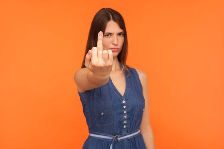 Impolite annoyed brunette woman in denim dress showing middle finger to camera, expressing protest hate and disrespect, gesturing fuck off rude symbol. indoor studio shot isolated on orange background Stock fotó
