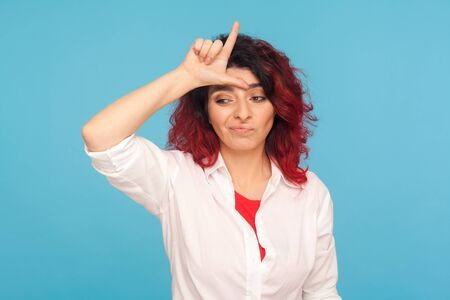 I'm loser! Portrait of unlucky depressed hipster woman with fancy red hair showing L sign on forehead, making loser gesture and feeling insecure, disappointed with defeat. studio shot blue background