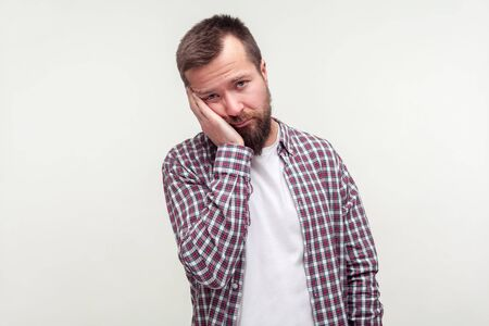 Portrait of bored young bearded man in plaid shirt leaning on hand with dull lazy face expression, depressed indifferent look, tired of everything. indoor studio shot isolated on white background
