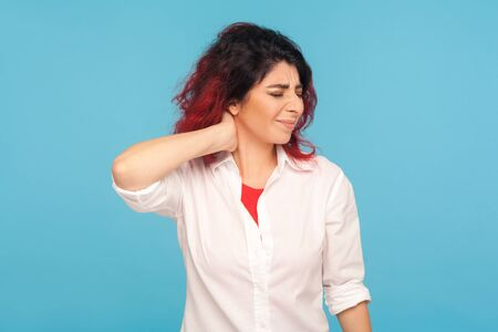 Fatigue, overwork. Portrait of tired office worker in white shirt rubbing painful neck, feeling discomfort from muscle tension, hurting shoulders. indoor studio shot isolated on blue background
