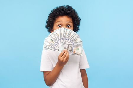 Amazed cute funny little boy with curly hair in T-shirt hiding half face with money and peeking out of dollar bills with astonished shocked eyes. indoor studio shot isolated on blue background Banco de Imagens
