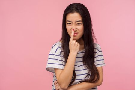 Portrait of girl with long hair in striped t-shirt touching nose, gesturing you are liar, being distrustful of talk, suspecting falsehood. indoor studio shot isolated on pink background