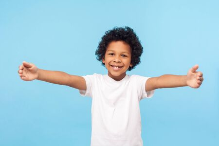 Portrait of lovely good-natured little boy with curly hair in white T-shirt smiling excitedly and holding hands wide open to embrace, greeting. indoor studio shot blue background