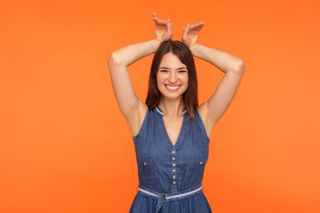 I'm bunny! Smiling funny amusing brunette woman in denim dress showing rabbit ears gesture on head and looking with childish carefree expression. indoor studio shot isolated on orange background Reklamní fotografie