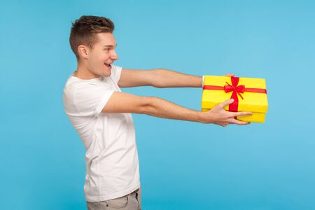 Charity and generosity. Side view of happy man in white t-shirt giving gift box and smiling with good-natured expression, offering birthday present. indoor studio shot isolated on blue background