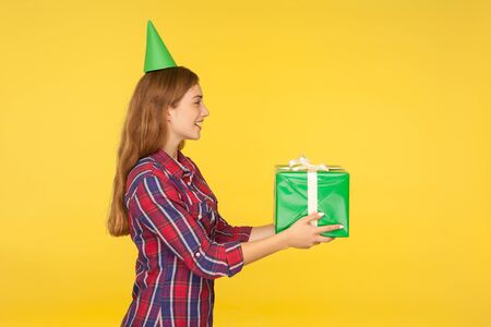 Side view of beautiful positive good natured girl with funny party cone on head giving present and saying congratulations, offering gift box, charity. indoor studio shot isolated on yellow background Stock fotó