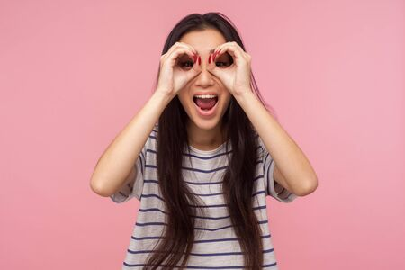 Portrait of overjoyed surprised girl with long brunette hair looking through binoculars shaped with fingers, zooming at camera and expressing shock, amazement. studio shot isolated on pink background
