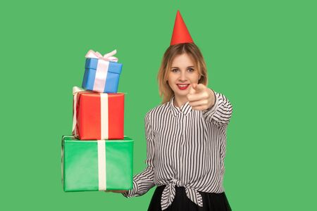 Good-natured happy woman with funny party cone on head pointing to camera and holding many gift boxes, choosing you to get presents and bonus, congratulating on birthday. studio shot green background