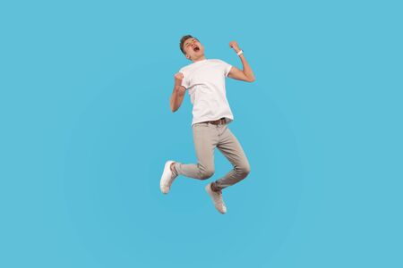 Full length, excited successful man in white t-shirt and casual pants jumping with happiness and shouting yes, I did it, feeling inspired and energetic. indoor studio shot isolated on blue background