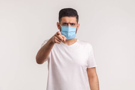 Hey you, use filters against novel influenza! Man pointing at camera and wearing hygienic mask to prevent coronavirus infection, respiratory diseases such as 2019-nCoV, ebola. studio shot, isolated