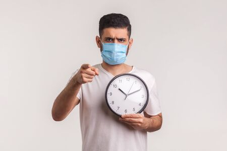 Time to be cautious! Man in protective hygienic mask holding clock, warning of novel virus epidemic, quarantine and risk during incubation period. indoor studio shot isolated on white background Stock Photo