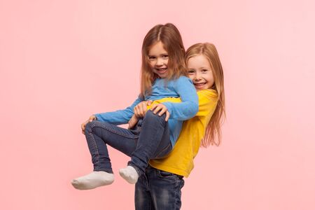 Portrait of cute preschool girl lifting up her little sister and smiling, friends having fun together, playing game, expressing carefree childish happiness. studio shot isolated on pink background