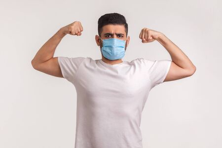 Man in hygienic mask showing strength and immunity to recover from contagious disease, airborne respiratory illness such as flu, coronavirus 2019-nCoV. indoor studio shot isolated on white background Reklamní fotografie