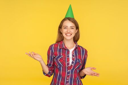 Birthday celebration. Portrait of happy beautiful ginger girl with funny party cone on head showing questioning gesture with raised hands and laughing. indoor studio shot isolated on yellow background Zdjęcie Seryjne