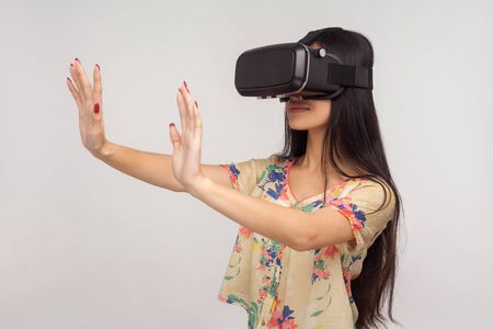 Young pretty woman in VR glasses standing with raised palms and positive calm facial expression, playing video game, using virtual reality 3d headset. indoor studio shot isolated on gray background