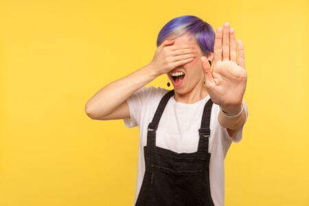 No, i don't want to look. Portrait of shocked girl with violet hair in denim overalls covering eyes and showing stop gesture, rejecting something shameful or scaring. yellow background, studio shot