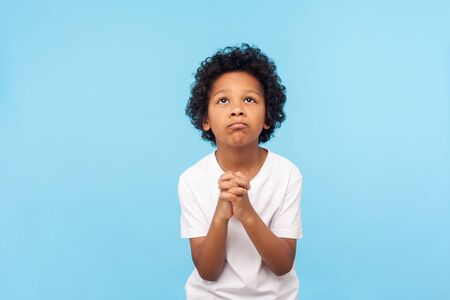 Please, I'm begging. Portrait of upset little boy praying to god with hands held together, apologizing for bad behavior, looking up with imploring eyes. indoor studio shot isolated on blue background
