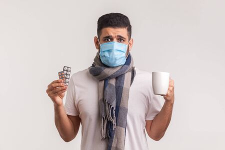 Portrait of scared man in protective hygienic mask holding pills and tea cup, looking desperate at camera, treatment of flu, contagious disease. indoor studio shot isolated on white background Stock Photo